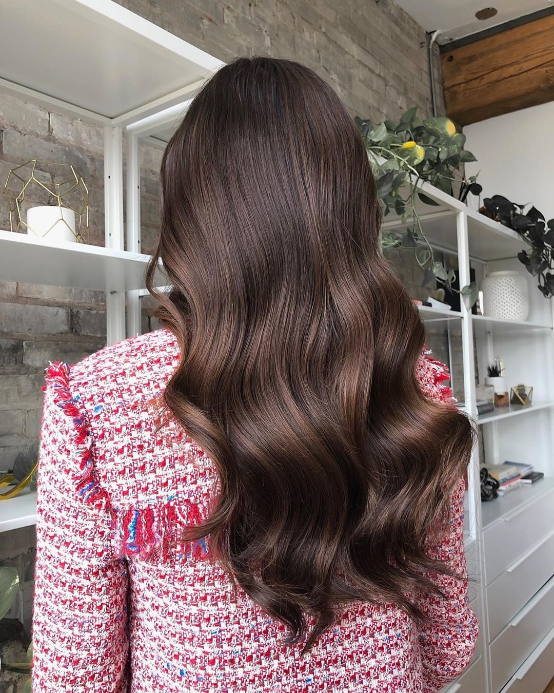 Woman with long glossy wavy chocolate brown hair