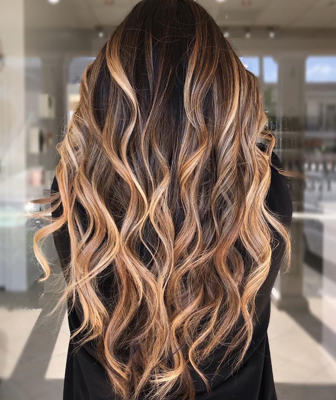 Woman with long curly bronde balayage hair
