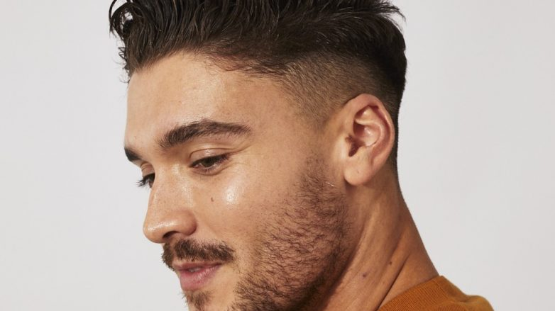 Brown haired man with a messy pompadour quiff and a fade
