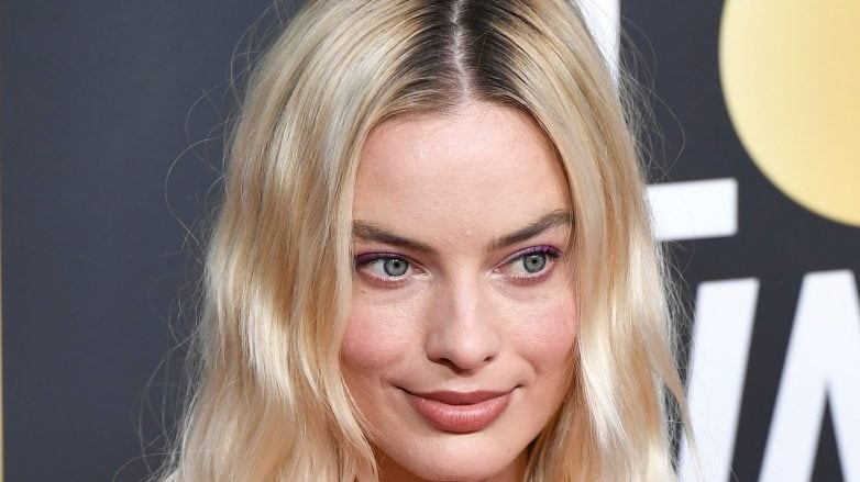 Margot Robbie with wavy blonde mid-length hair with dark roots