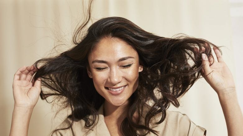 Woman with brunette long hair blowing in the wind