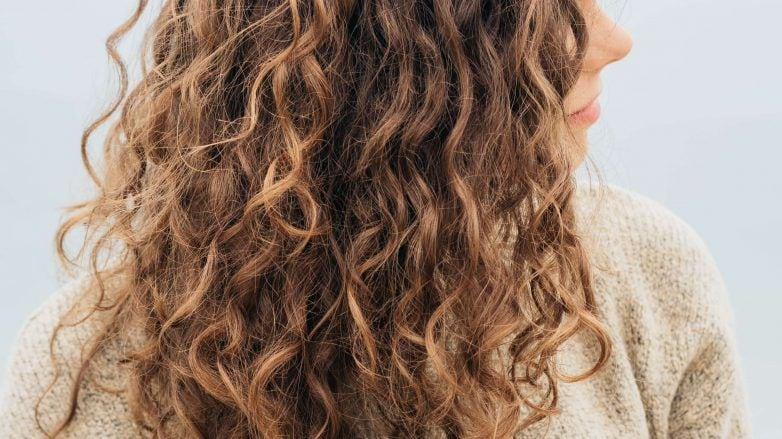 Woman touching her curly long hair