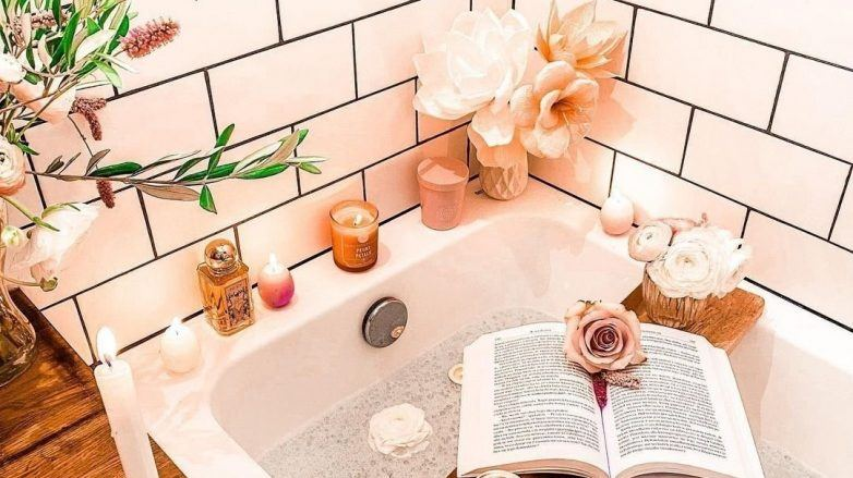 Photo of a bath with relaxing candles and a book