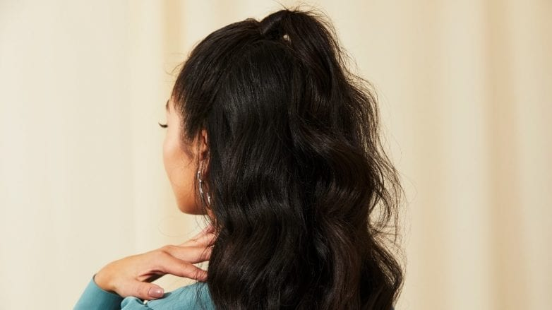 Woman with long dark brunette wavy hair in a half-up ponytail