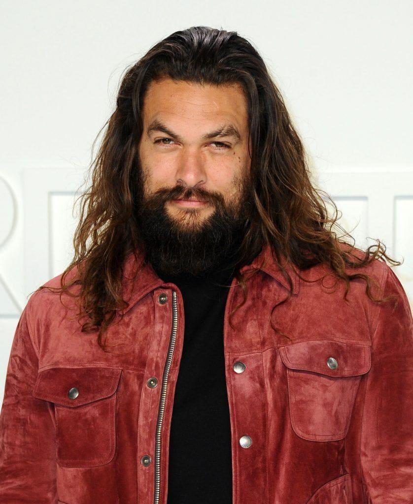 Jason Momoa with long brown wavy hair with facial hair
