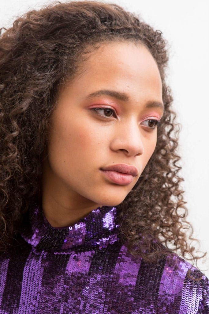 rizos virgen modelo con blusa púrpura