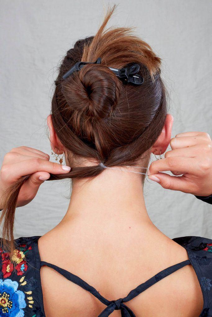raya del cabello a medio lado haciendo una cola