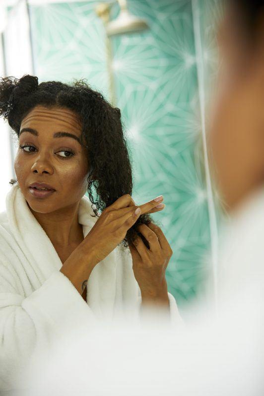 cómo usar aceite de coco en el cabello rizado
