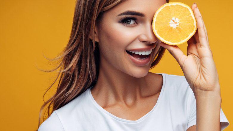 vitamina C mujer con naranja