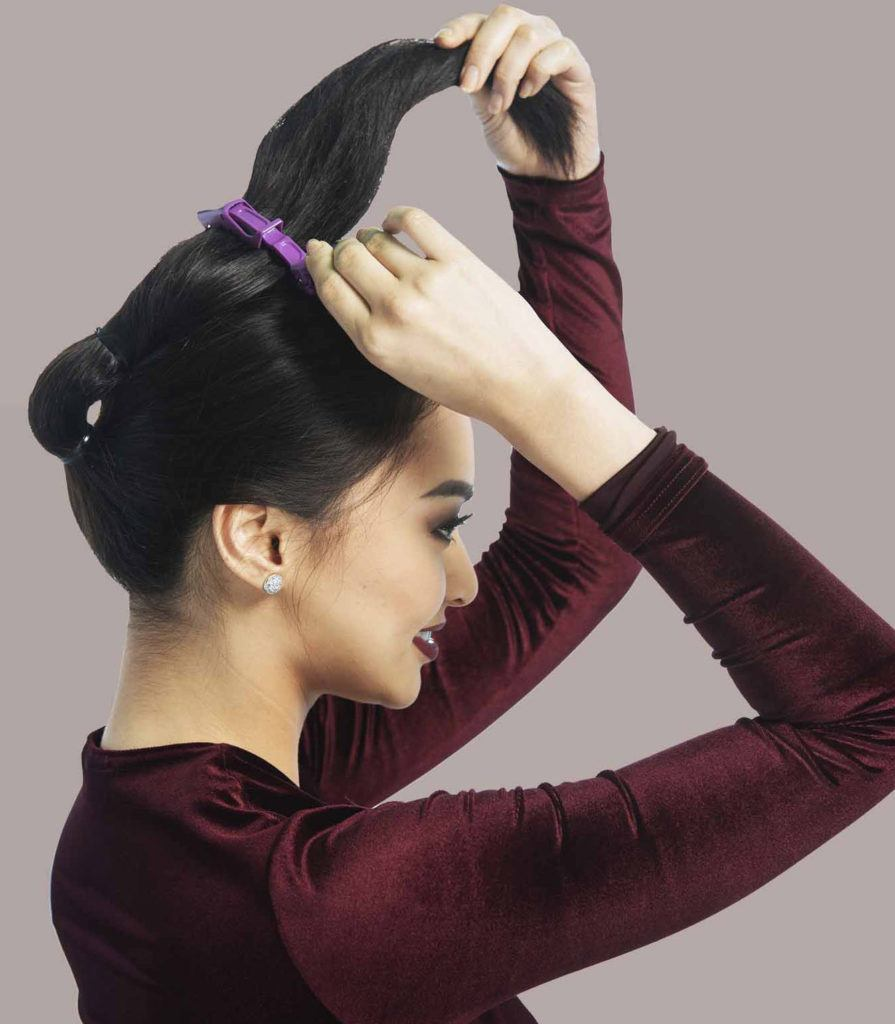 woman securing hair with a clamp up top