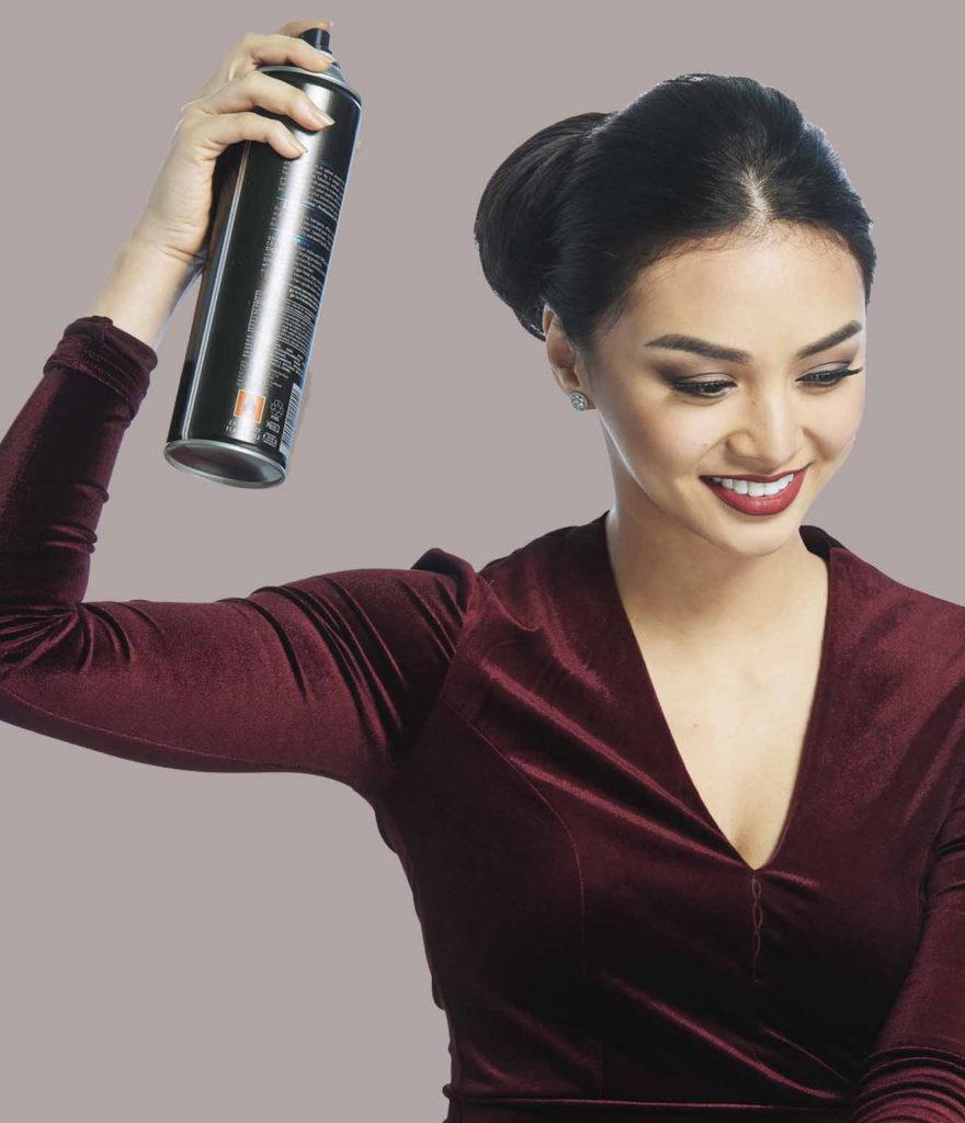 woman with bun using hairspray