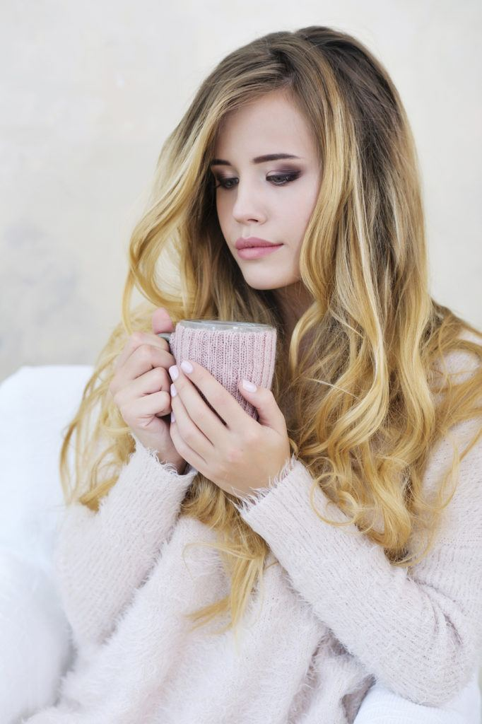 girl with blonde balayage and holding cup