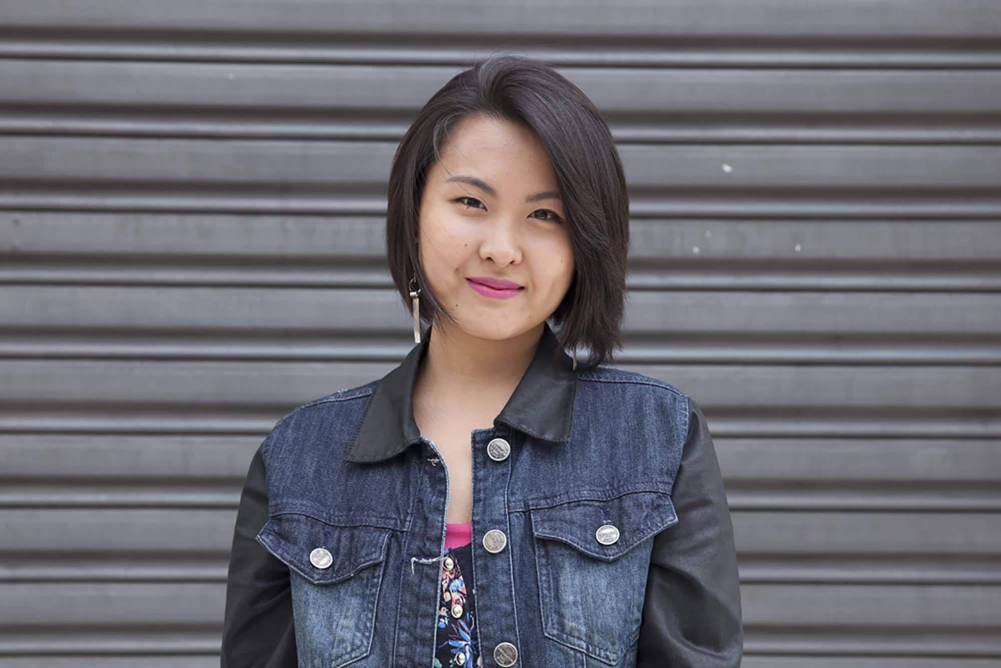 Short hair for round face: Asian woman with black hair in a bob wearing a denim jacket outdoors