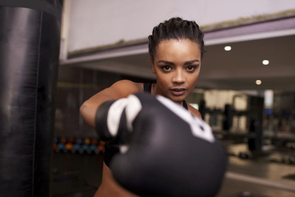 Portrait of a young woman with boxing gloves punching at the camera while at the gym