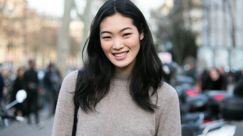 asian girl with medium length haircut standing on street