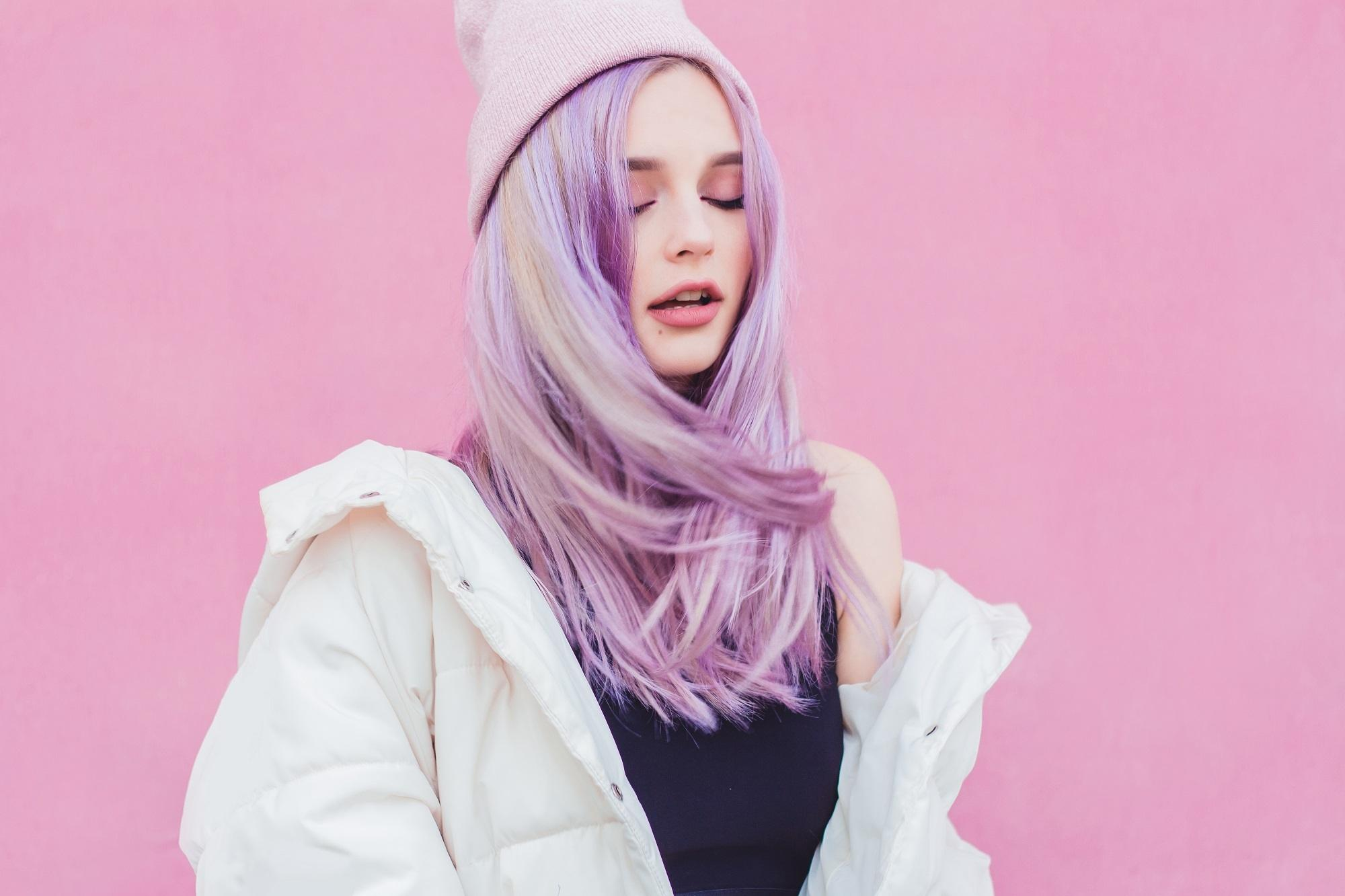 Hair color for fair skin: White woman with long lilac hair wearing a white jacket and white bonnet against a pink background