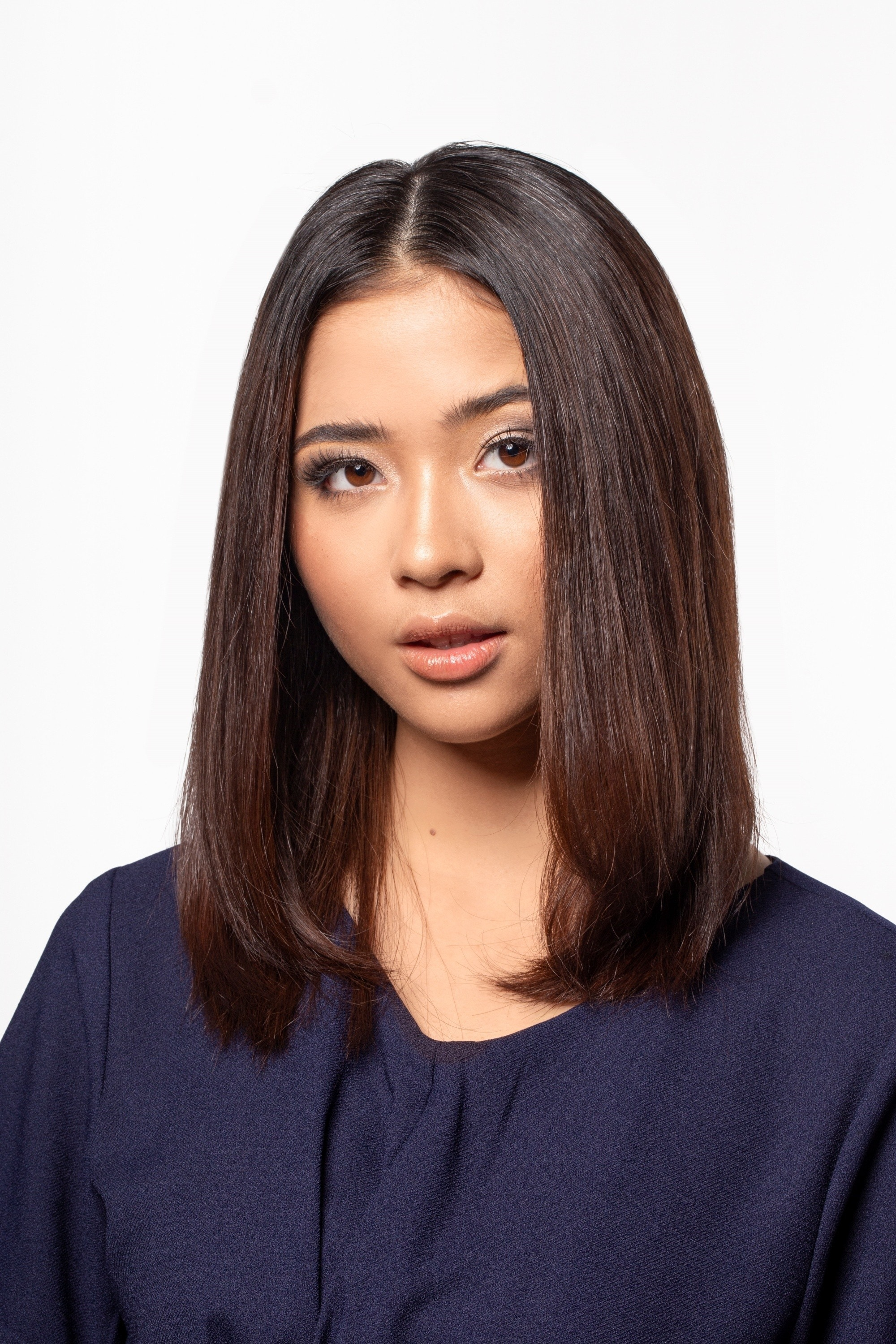 Hair facts: Asian woman with shoulder-length dark hair wearing a dark blue top