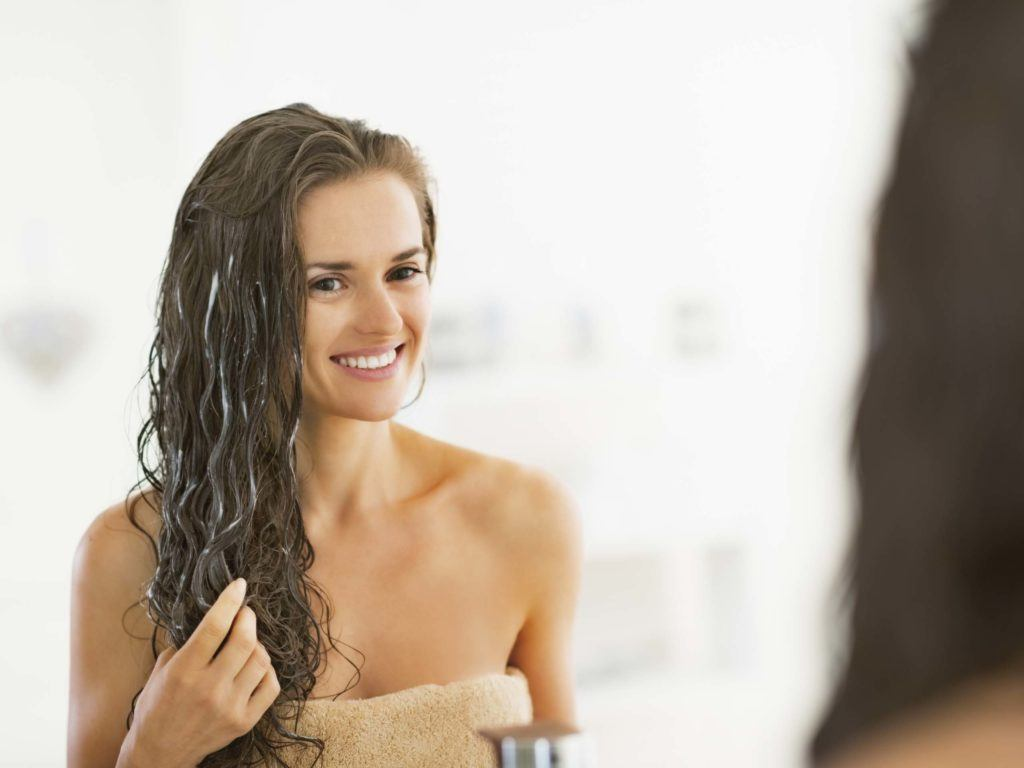Woman using the best conditioner for her hair in the bathroom