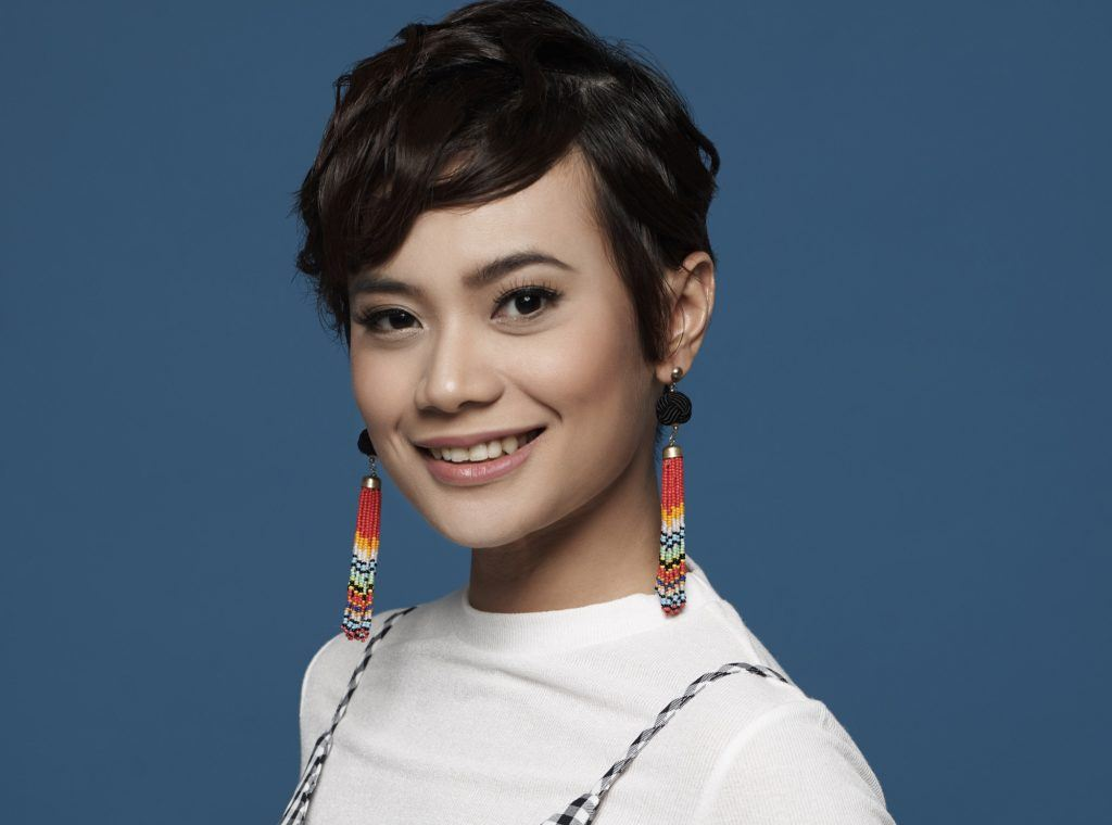 Hairstyles for thin hair: Closeup shot of an Asian woman with black messy textured pixie cut wearing dangling earrings and a white shirt