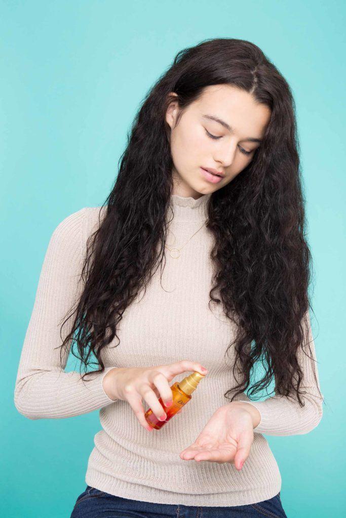 woman applying hair serum to hair