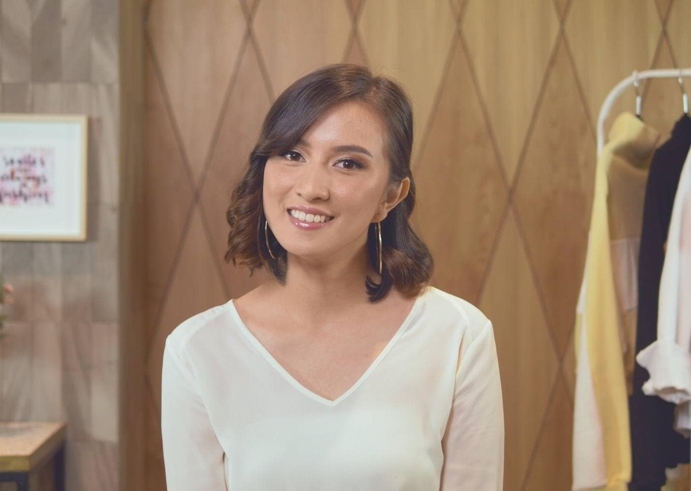 Asian woman with wavy bob with side part wearing a white V-neck top smiling