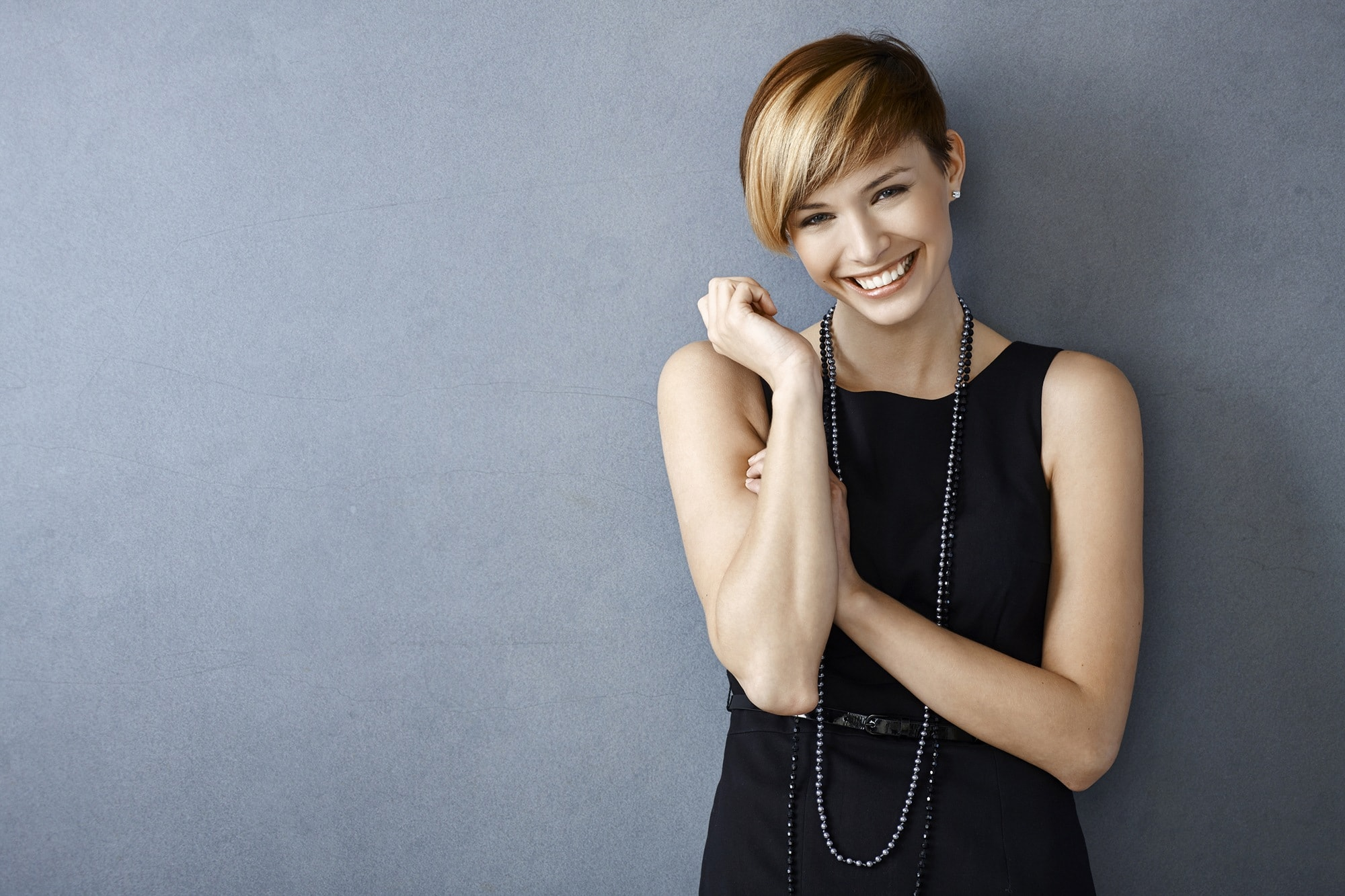 Short hair for round face: Woman with short blonde hair in pixie cut with long bangs