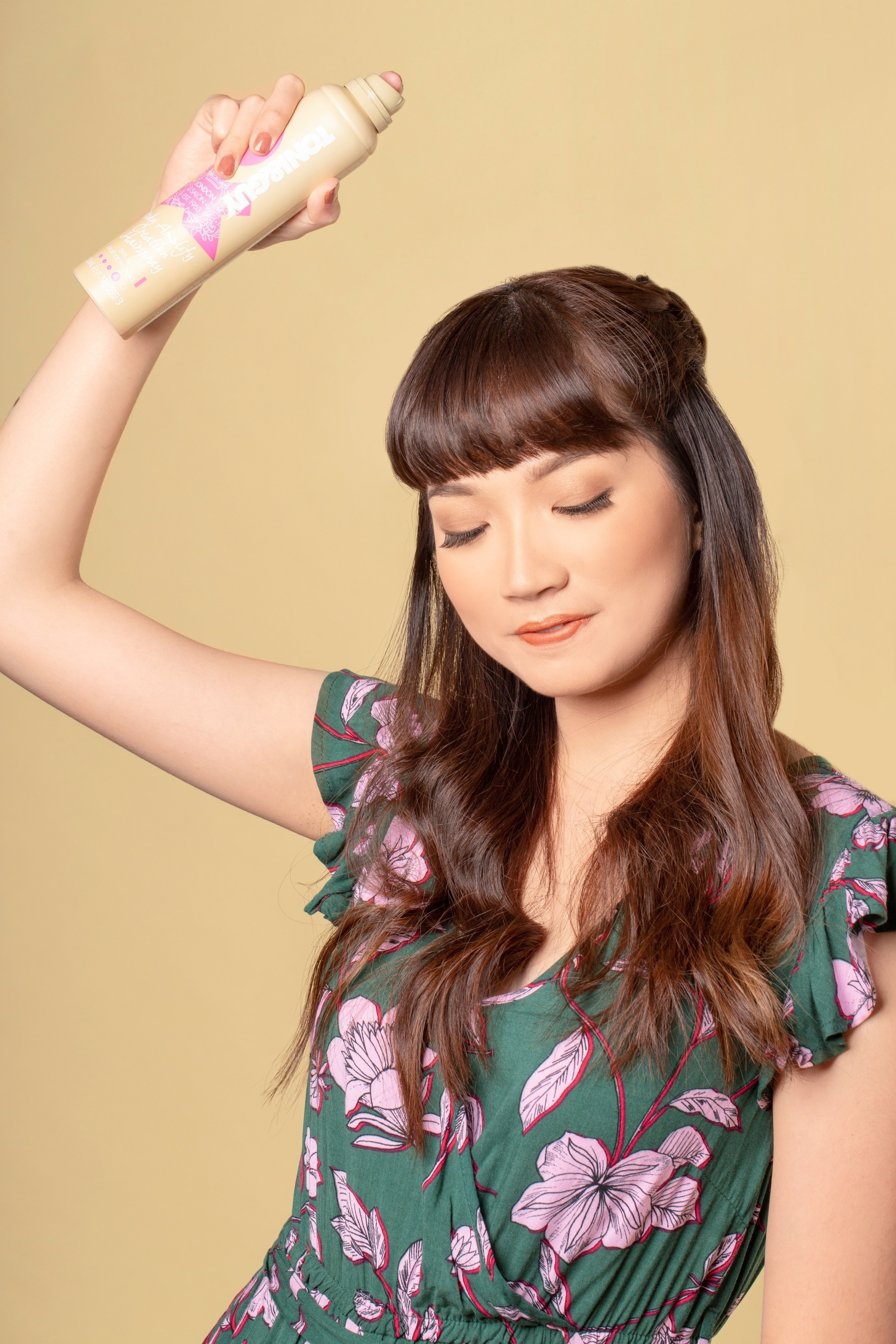 Hair spray guide: Asian woman spraying on her long hair