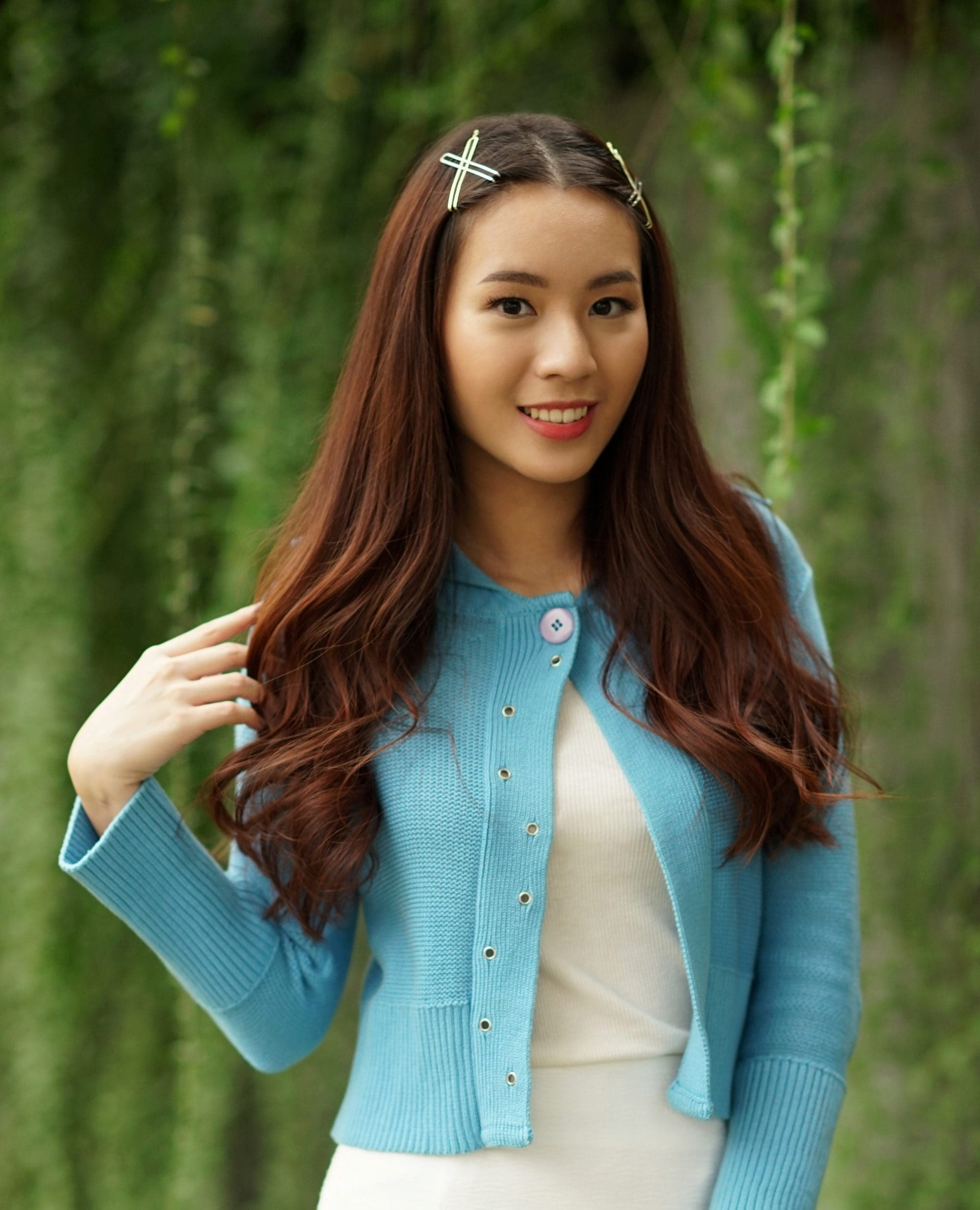 Heat protectant: Asian woman with long dark wavy hair with hair clips wearing a blue cardigan and white dress outdoors