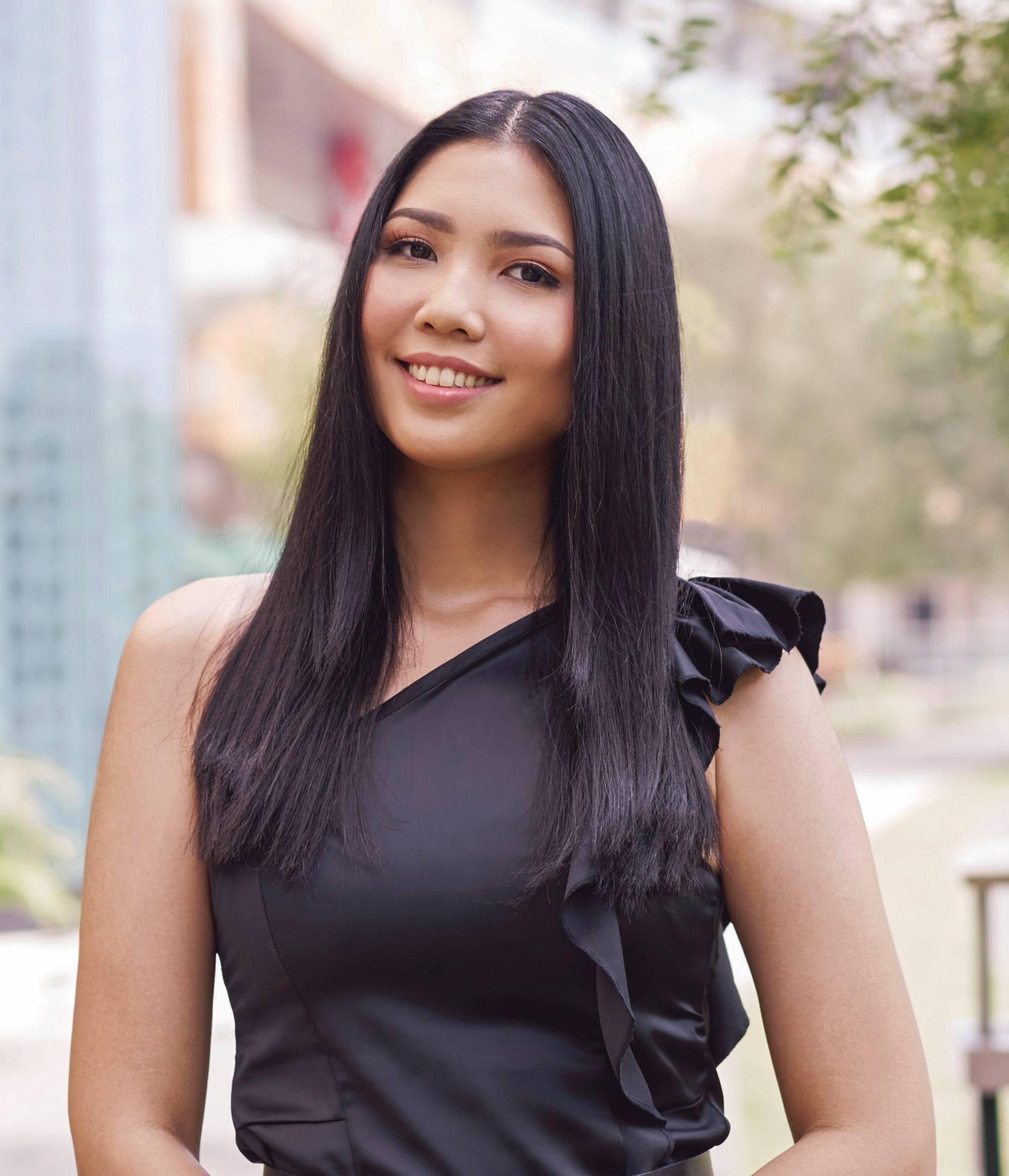 Heat protectant spray: Closeup shot of an Asian woman with long straight black hair wearing a black dress outdoors