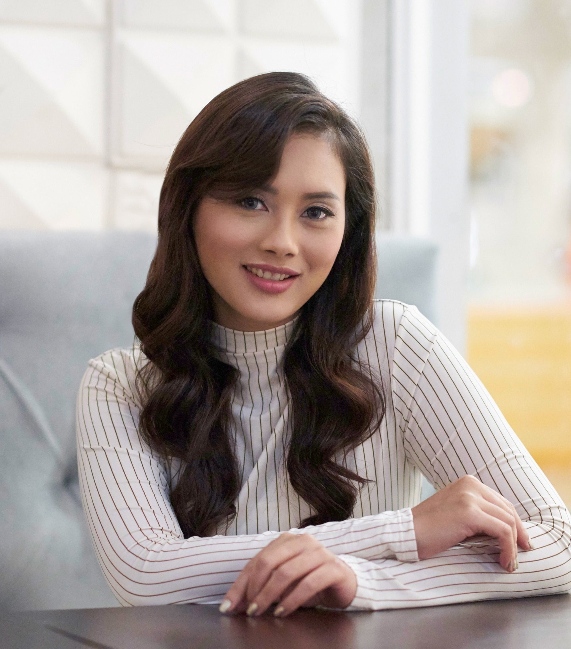 Heat protectant spray: Closeup shot of an Asian woman with long dark wavy hair wearing a white long-sleeved top in a cafe