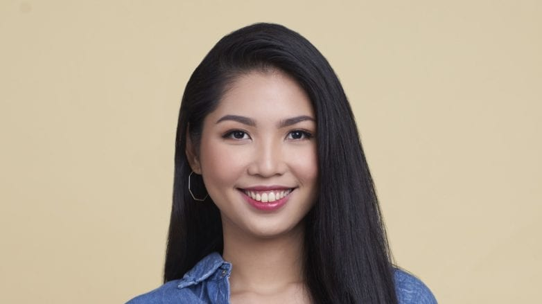 Oily hair: Asian woman with long black straight hair wearing a denim jacket against a pale yellow background
