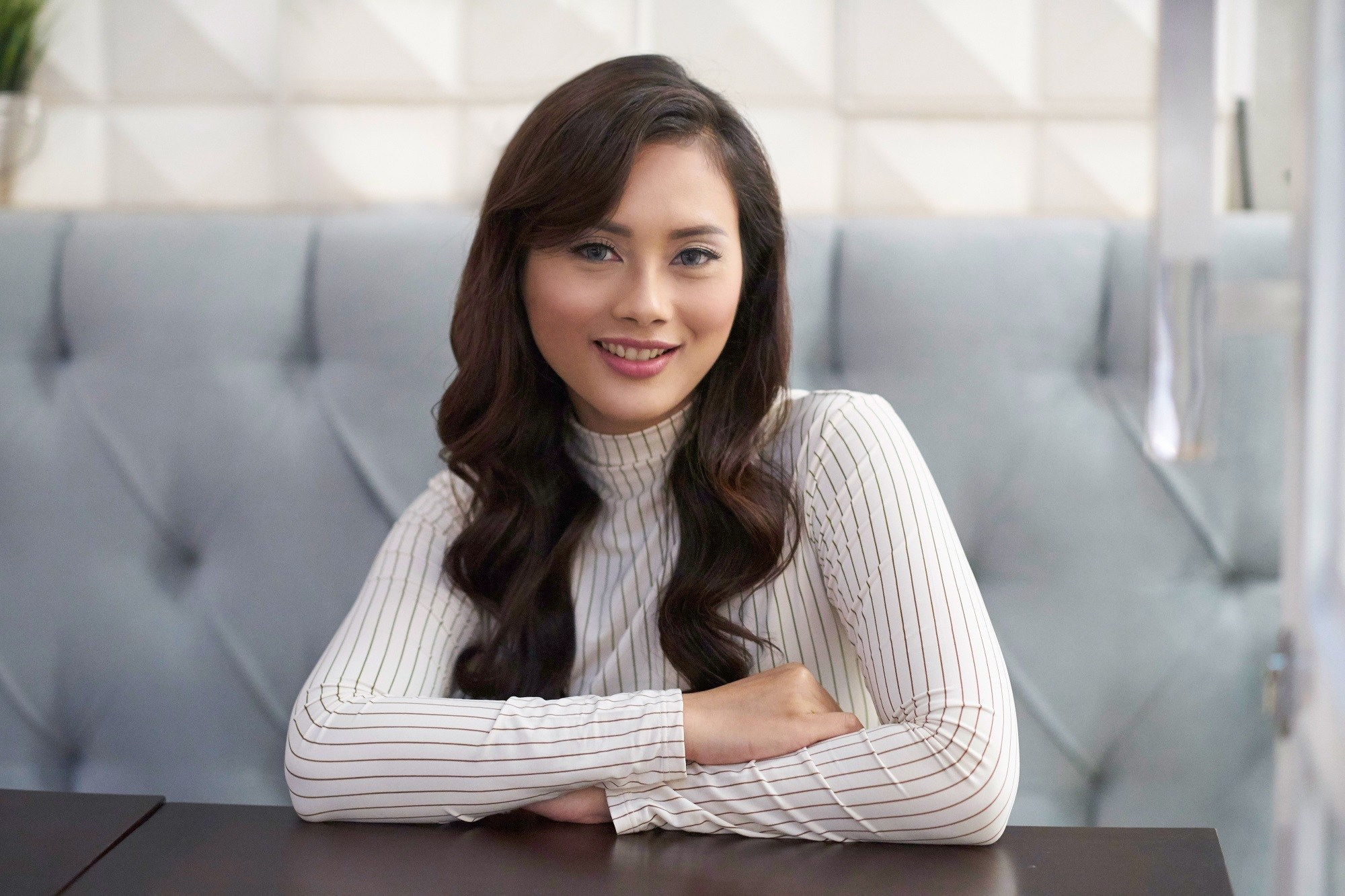 Oily hair: Asian woman with long dark wavy hair wearing a white long-sleeved top sitting on a sofa