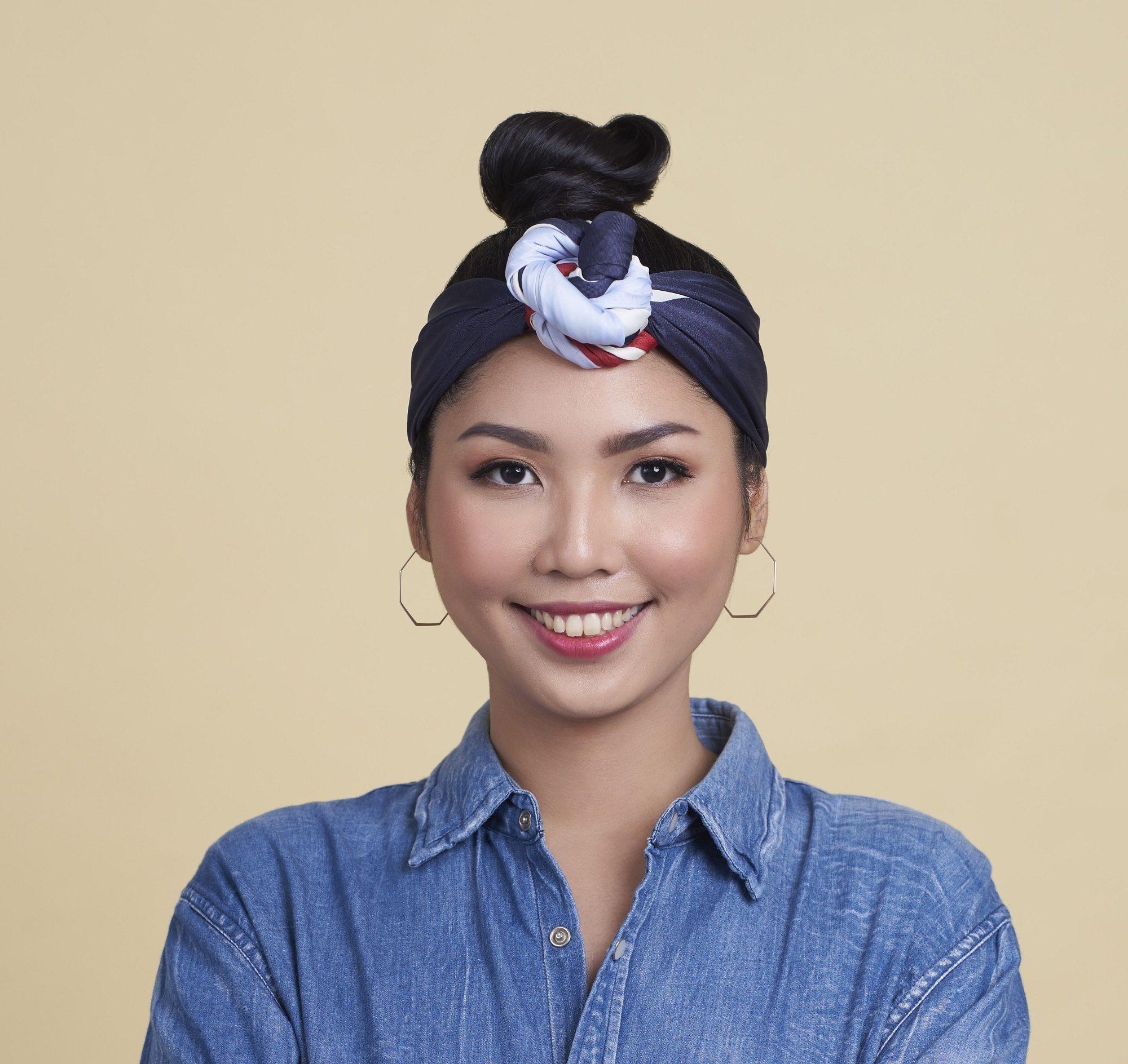 Oily hair: Closeup shot of an Asian woman with black hair in a top bun with headband
