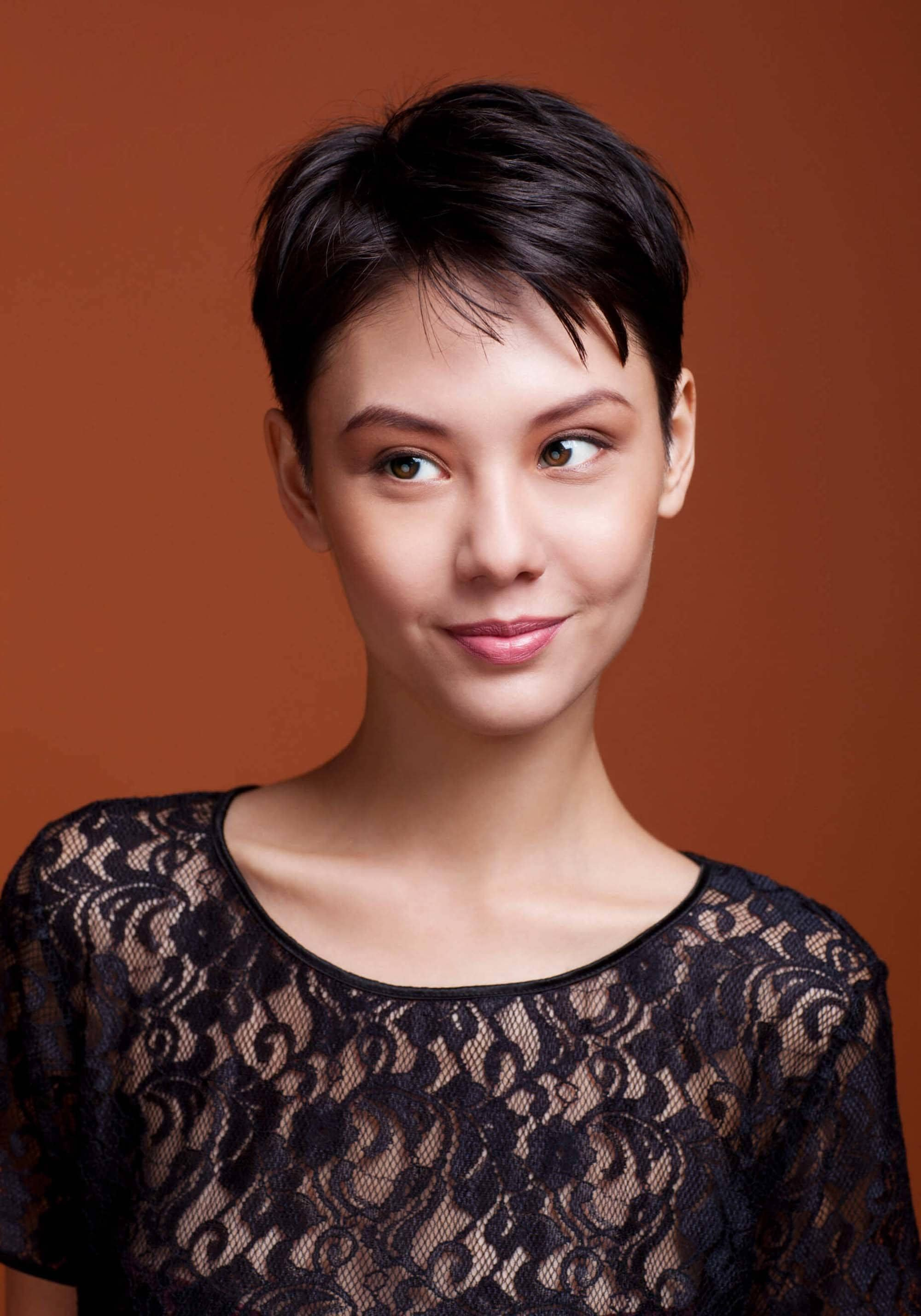 Haircuts for rainy season: Asian woman with a shirt pixie, wearing a black lace top