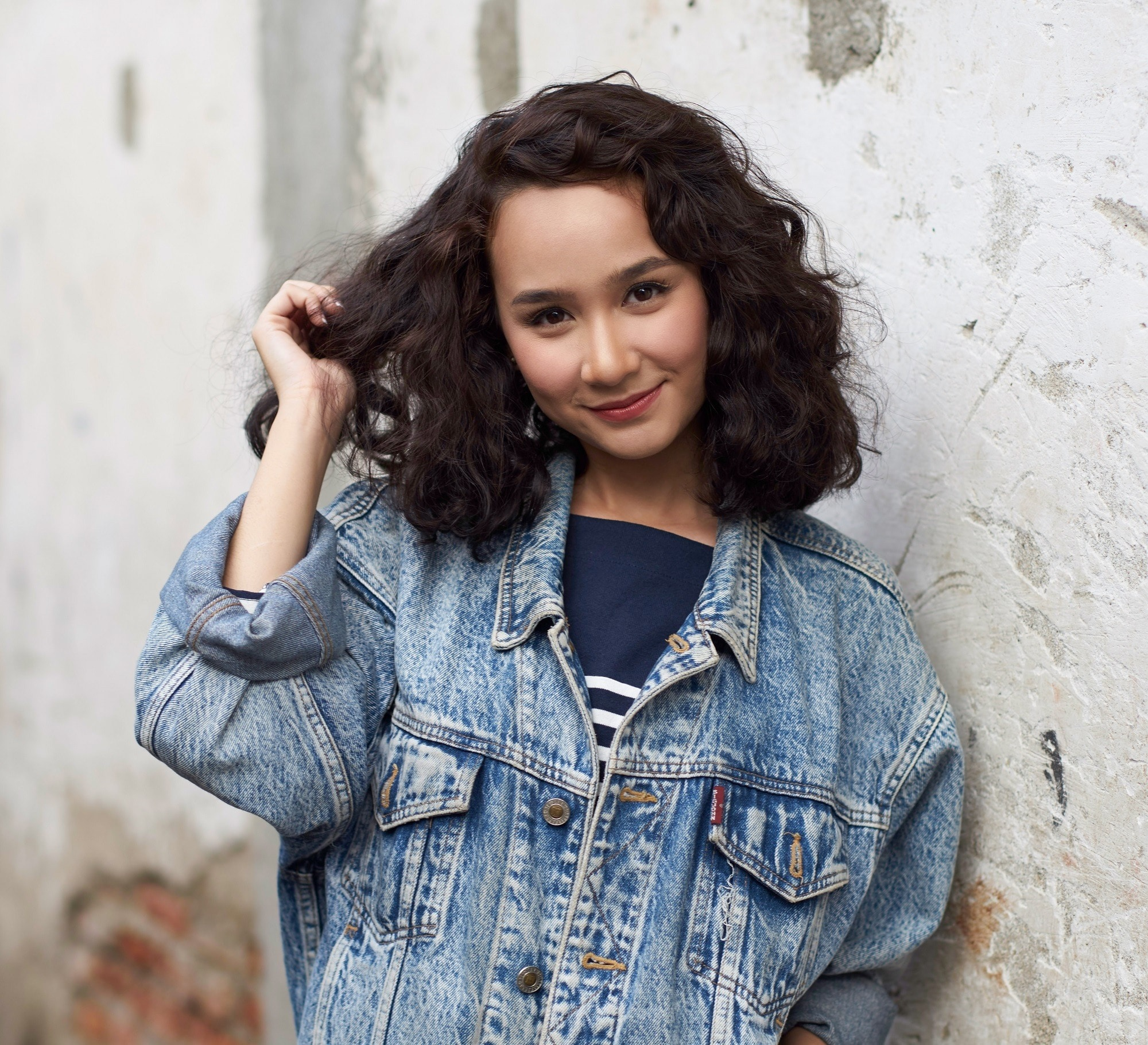 Frizzy hair remedies: Closeup shot of Asian girl touching her black curly hair wearing denim jacket against a stone wall