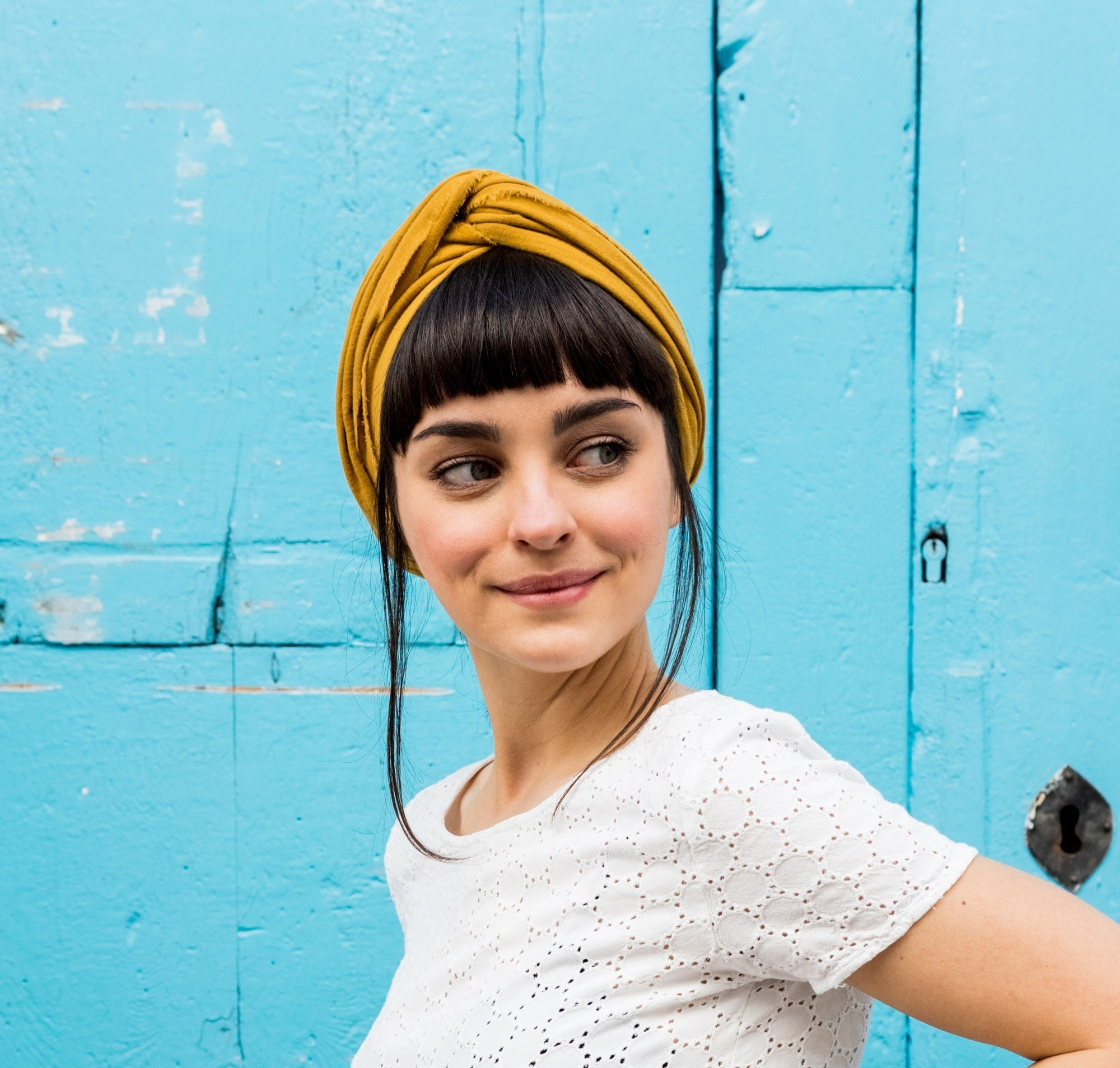 Styling blunt bangs: Closeup shot of a woman with black hair and blunt bangs wearing a mustard-colored headband