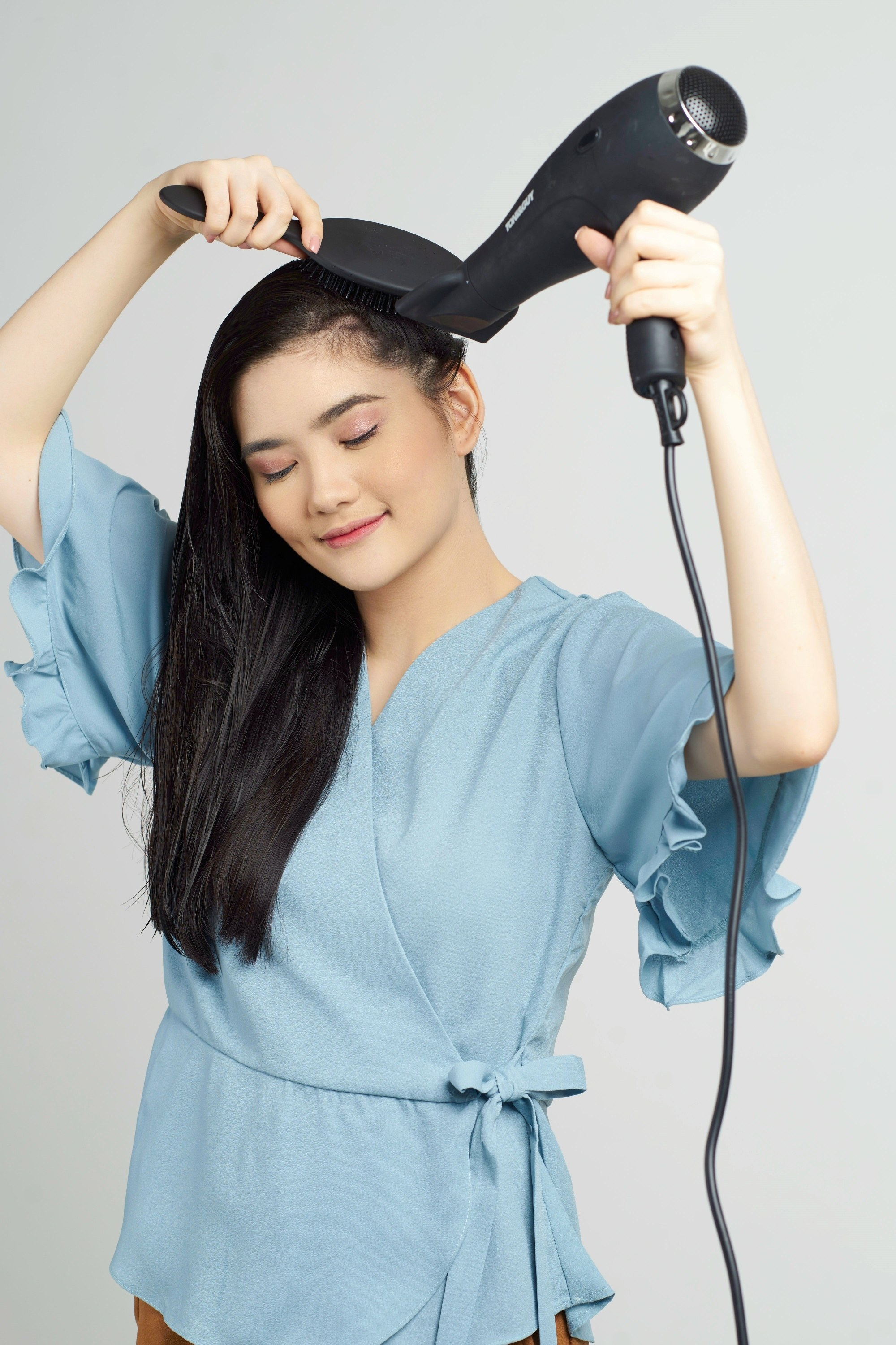 Keratin treatment at home: Asian woman blow drying and brushing her long straight black hair