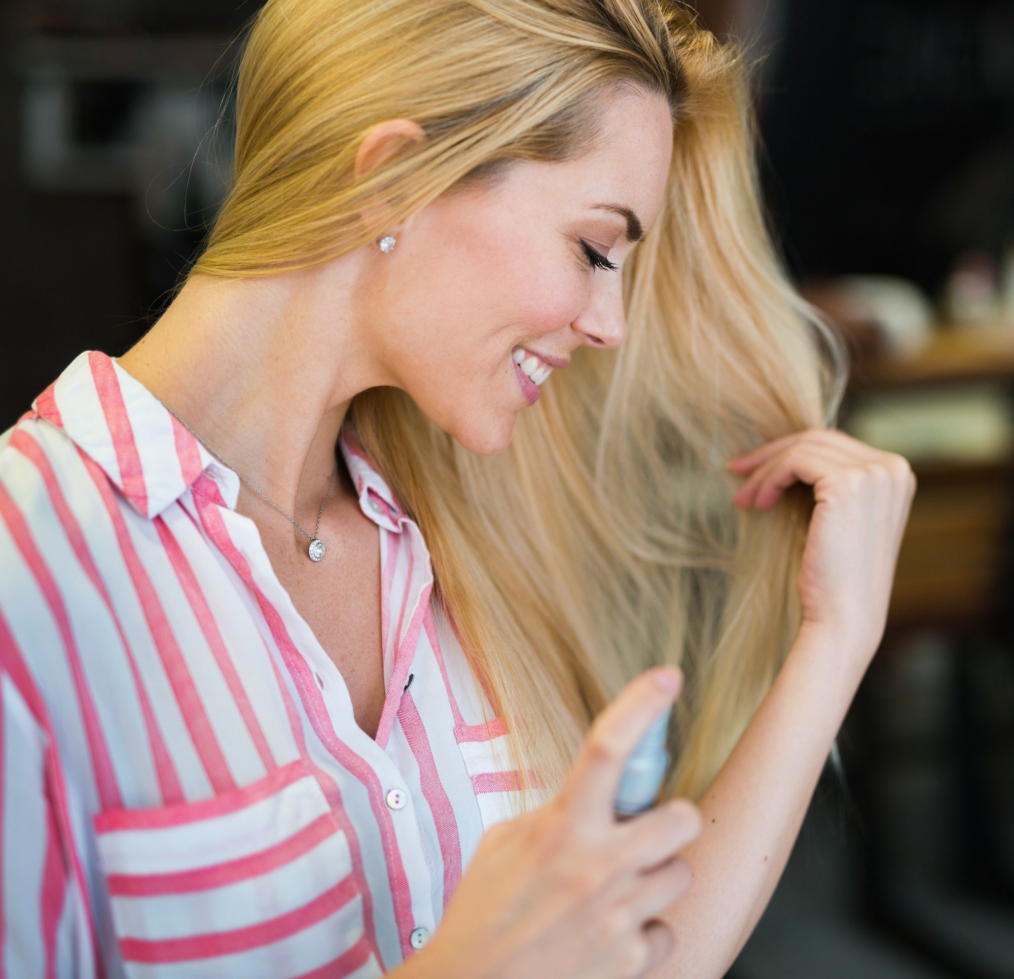 Hair care tips for traveling: Closeup shot of a woman with long blonde hair spraying her hair and wearing a striped blouse