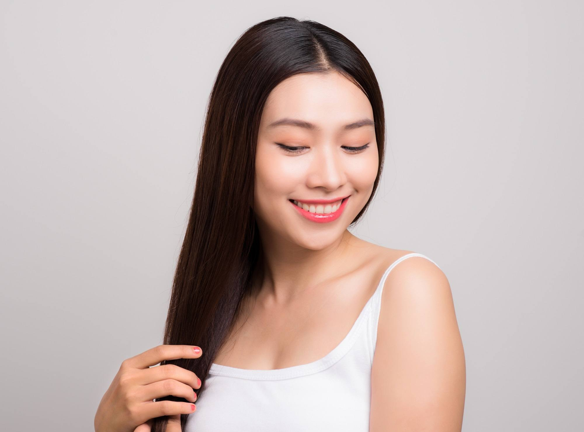 Hair care tips for traveling: Woman touching her long black straight hair wearing a white tank top against a gray background