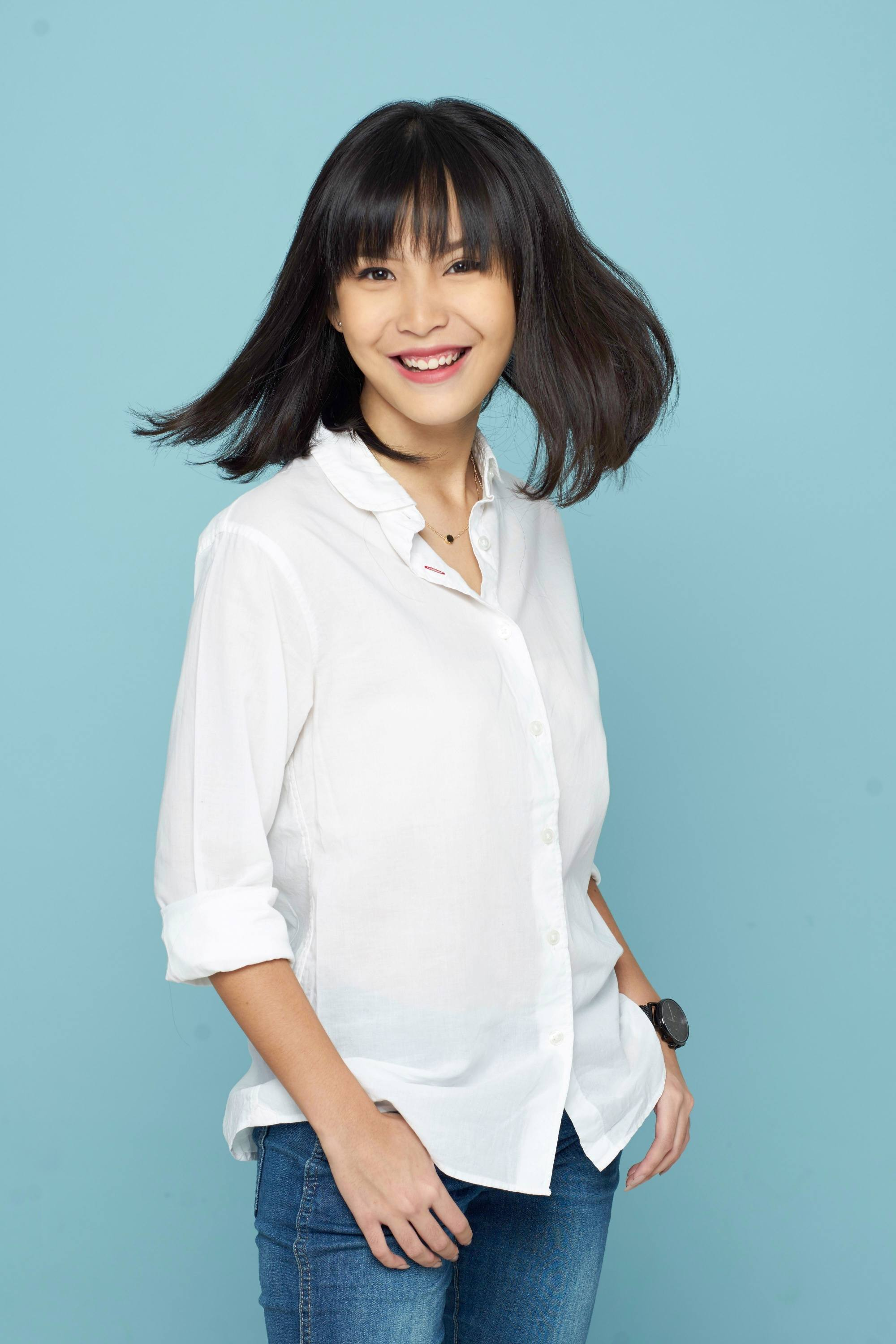 How to use leave-in conditioner: Asian woman with black medium-length hair with bangs wearing a white polo and jeans