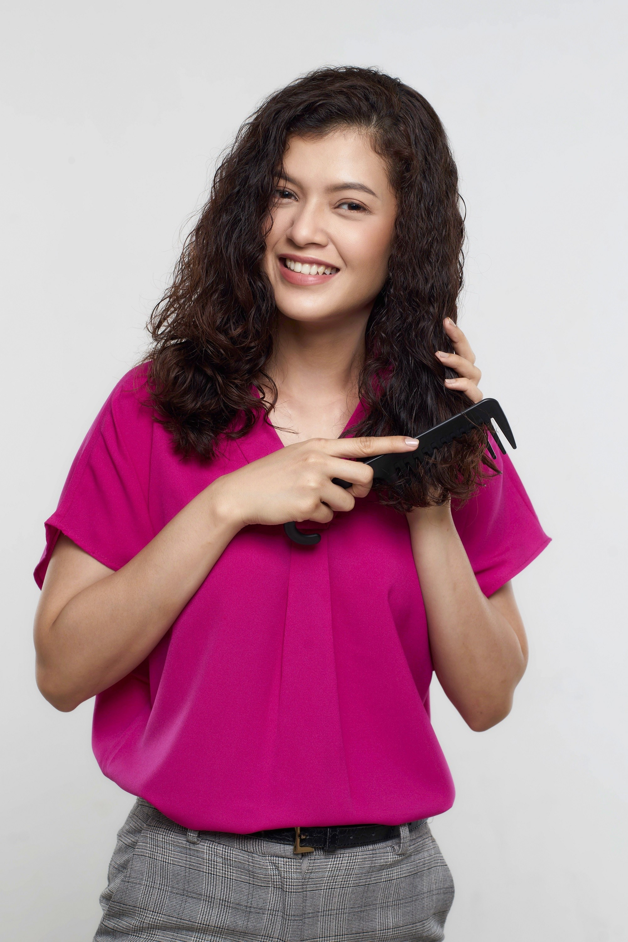 How to use leave-in conditioner: Asian woman combing her shoulder-length dark curly hair and wearing a pink blouse