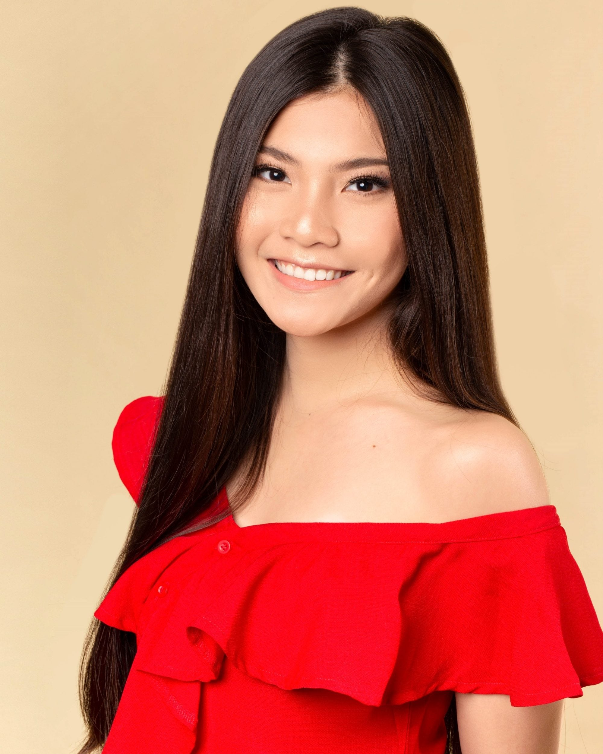 Asian woman with long dark brown straight hair wearing a red top