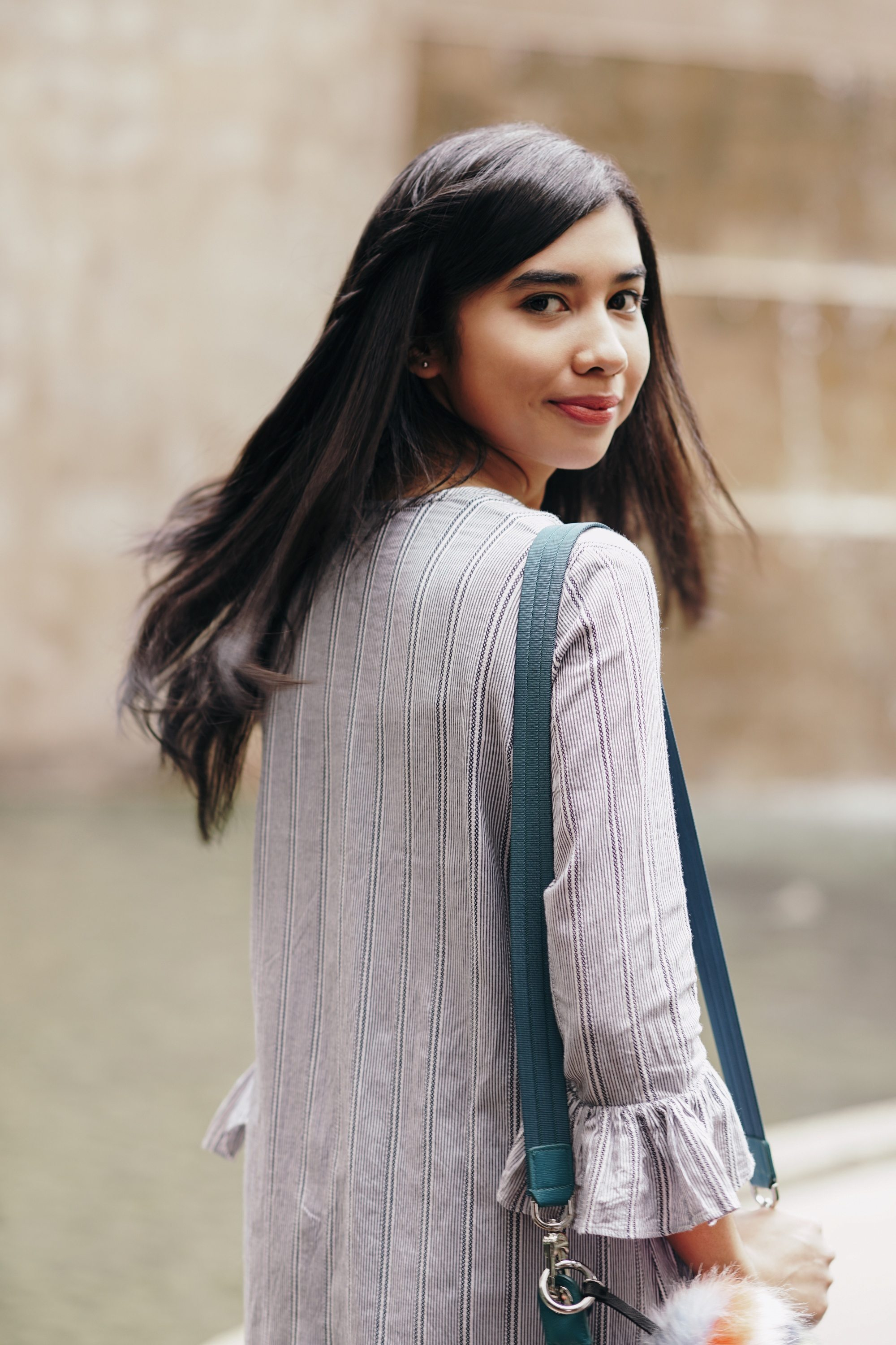 Asian woman with long black layered hair wearing a cardigan