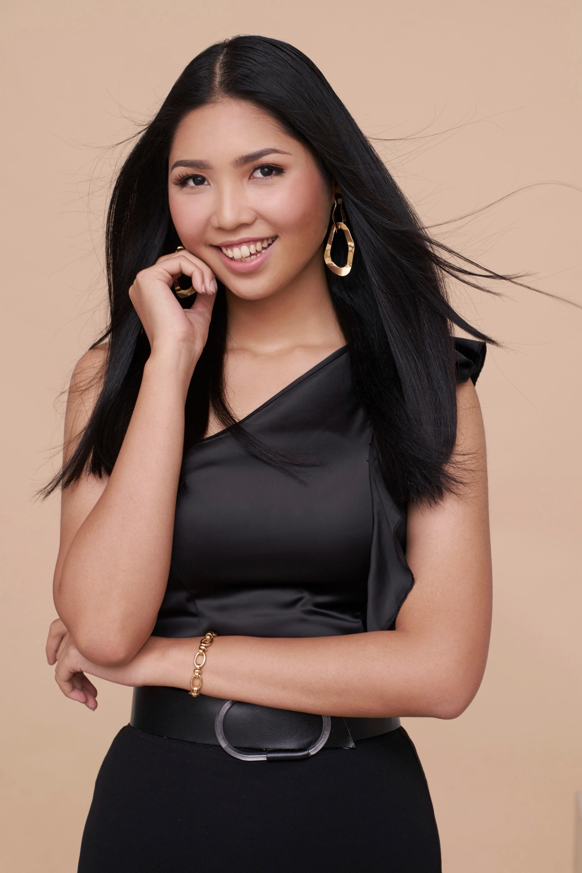 Keratin condiioners: Asian woman with wind-blown long black straight hair wearing a black dress