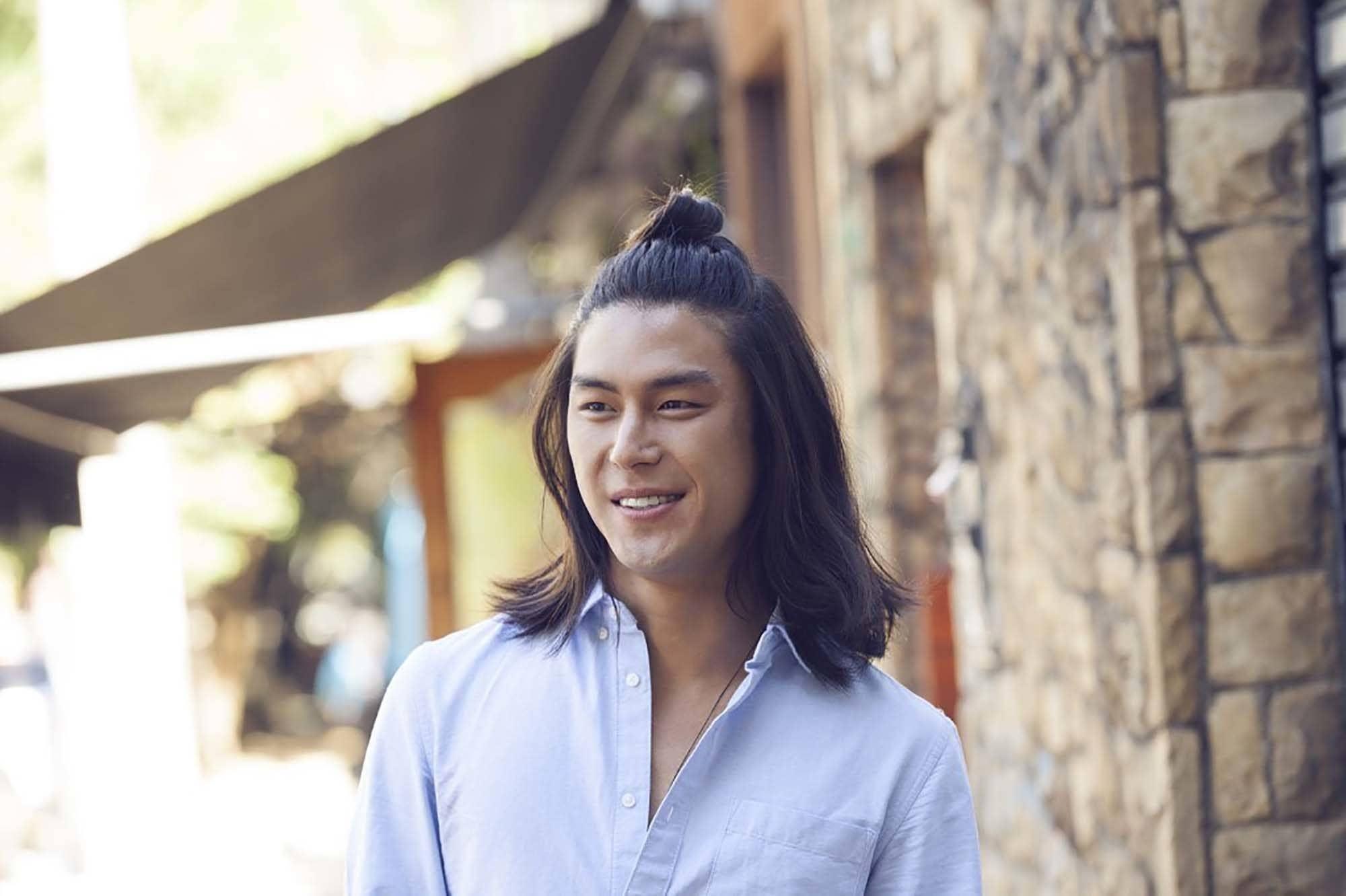 Asian man bun: Man with long black hair with a half up bun wearing a white shirt outdoors