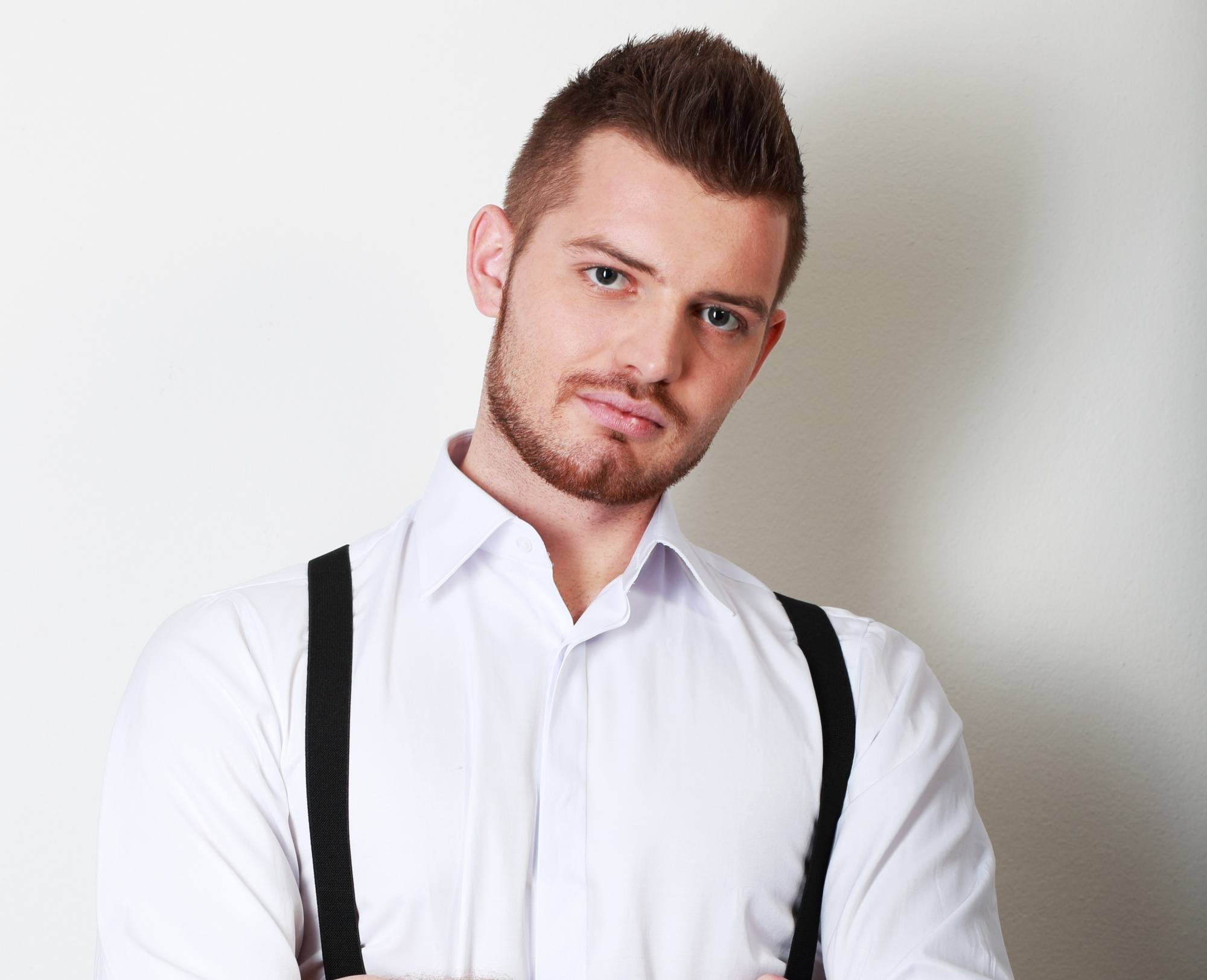 Pinoy haircut: Man with short dark hair wearing a white dress shirt and suspenders
