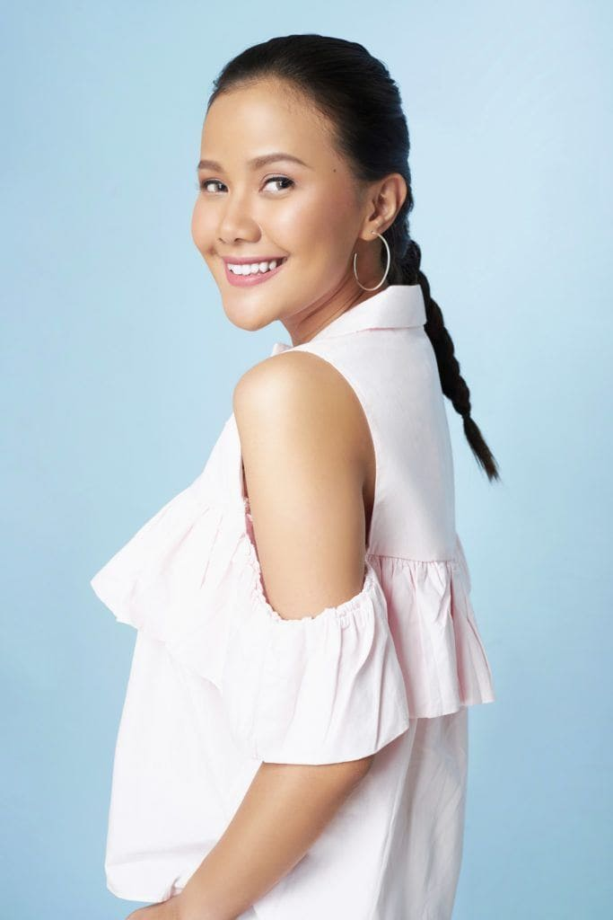 Easy commuter-friendly hairstyles: Asian woman with long black hair in a Dutch braid wearing a white blouse