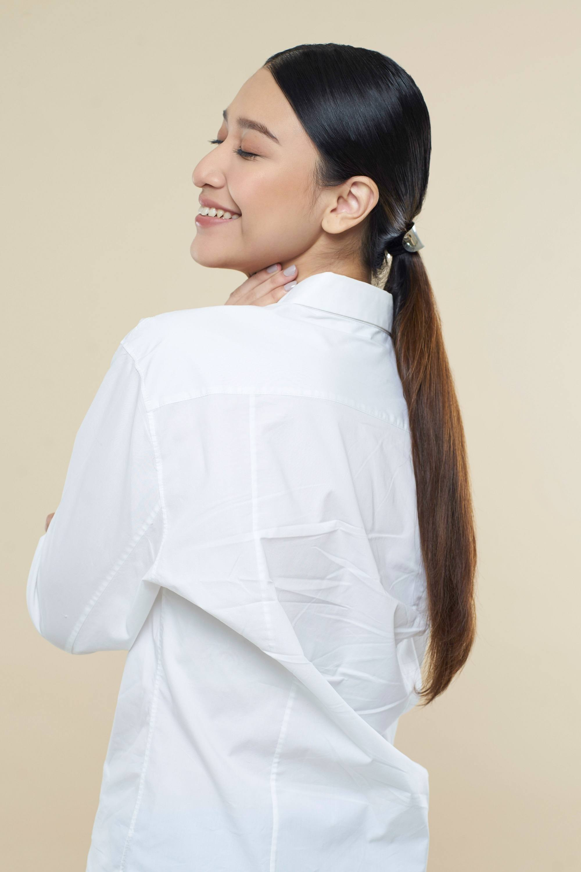 Easy commuter-friendly hairstyles: Side view of an Asian woman with long dark hair in a low ponytail wearing a white blouse