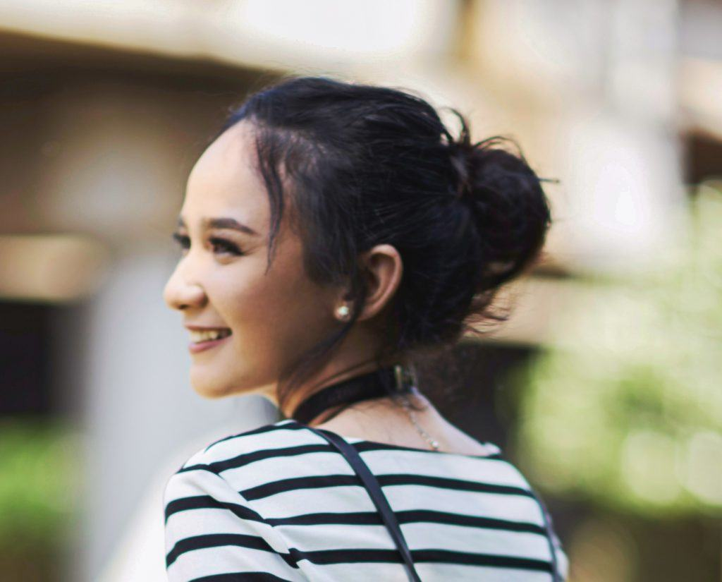 Asian woman with a messy bun hairstyle for commuters