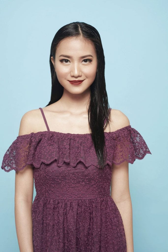 Asian woman with long black hair wearing a mauve dress